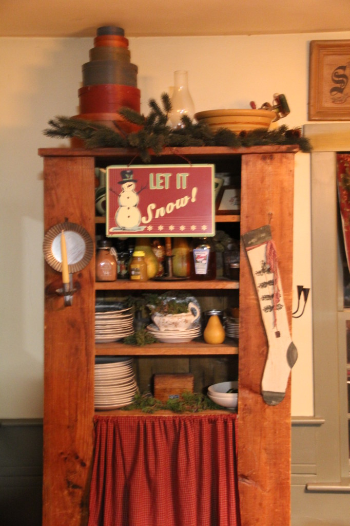 I absolutely love this antique jelly cabinet. It holds my extra dishes and behind the magic curtain I store home school resources.